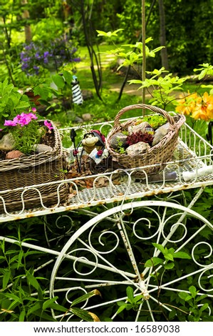 Flower cart with two baskets in summer garden