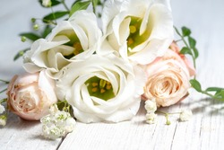 flower composition of light roses and eustoma close up. wedding day greeting card.