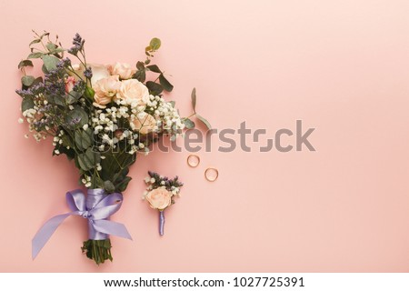 Flower composition, wedding bouquet with ribbon, boutonniere and two golden rings, lying on pink table. Wedding decor, artwork, florist, flat lay, top view