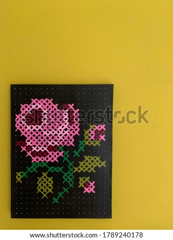 flower cross stitch painting on lime green wall