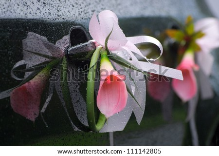 Flower decoration on dark wedding car with rain drops