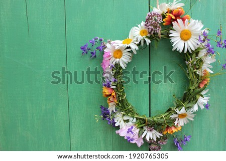 Flower door wreath. Midsummer flower crown on rustic wooden background with copy space. DIY floral wreath. Midsummer night dream decoration. Farm rustic lifestyle. Floral traditional decor