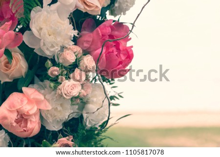 Flower frame from pink roses and peonies on beach background. Invitation, wedding, love, Valentine's, Mother's Day concept. Close-up, copy space, toned