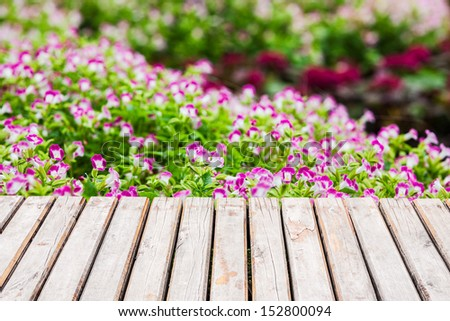 Flower garden with wooden platform - stock photo