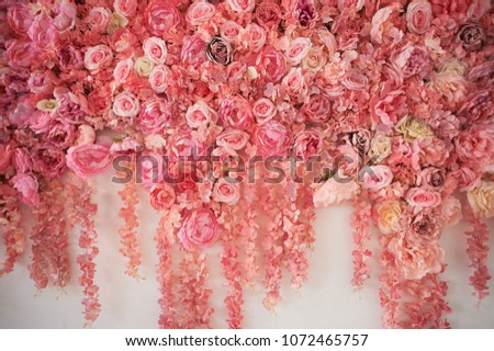 Flower garland on the wall. Dense wall of flowers. Wedding photo zone. Romantic space decor