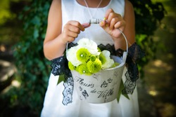 Flower girl at a wedding holding a basket of flowers.