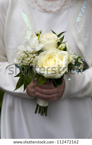 flower-girl or bridesmaid holds bouquet of white roses