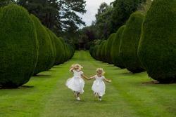 Flower girls holding hands running in park
