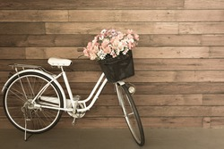 flower in basket of vintage bicycle on vintage wooden house wall