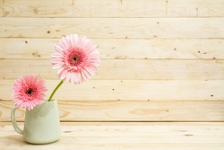 flower in cup with pine wood background.