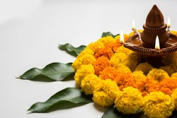 Flower Rangoli for Diwali or Pongal Festival made using Marigold or Zendu flowers and mango leaf and Clay Oil Lamp over white background, selective focus