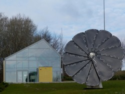 flower shaped solar panel, attractive & innovative intelligent rotating & turning to follow the sun's movement thereby garnering maximum efficiency. Under blue sky. self sustained glass house behind.