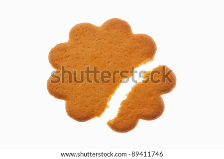 Flower shaped sugar cookie broken into two pieces, isolated on white, backlit.