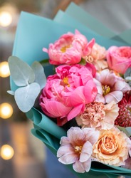 Flower shop. Beautiful bouquet of mixed flowers in woman's hands. the work of the florist at a flower shop. Delicate bright color. Fresh cut flower.