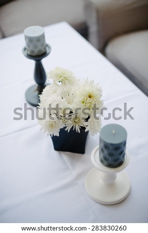 Flower vase in the shape of a cube and candlesticks standing next to the table ready to receive guests of the wedding ceremony.