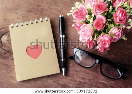 Flower with blank notepad and pen on old wooden background, Valentine\'s day and love concept