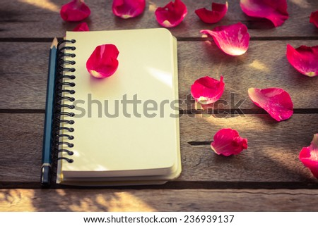 Flower with notebook on desk