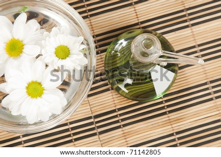flower with oil on wooden background