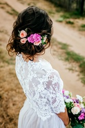 flower wreath in the hair, decoration on the head of the bride from fresh flowers, wedding day, image of the bride