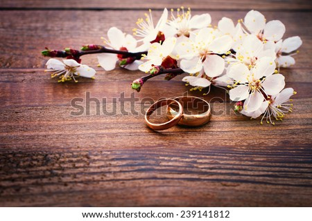 Flowering branch with white delicate flowers on wooden surface. Declaration of love, spring. Wedding card, Valentine\'s Day greeting. Wedding rings. Wedding bouquet, background.