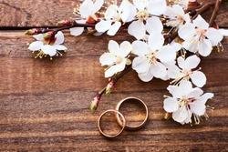 Flowering branch with white delicate flowers on wooden surface. Wedding rings. Wedding bouquet, background.