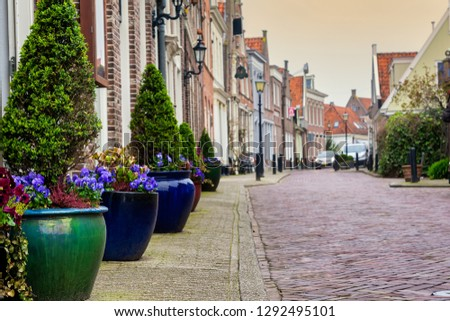 Flowerpots on the street side in a small city Edam in Netherlands. Edam is a small village in the district Nordholland, Netherlands.
