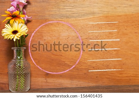 Flowers against a wooden background for texture with chalk outlines for copy space.