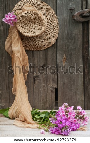 flowers and a straw hat against the background of the old wooden walls