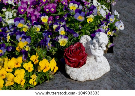Flowers and angel in front of a grave