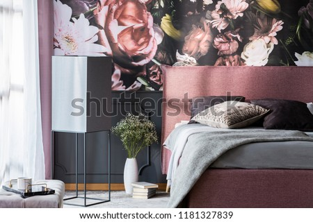 Flowers and books next to pink bed with grey pillows in patterned bedroom interior. Real photo