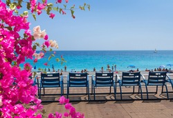 flowers and chairs in front of turquiose water of cote dAzur, France