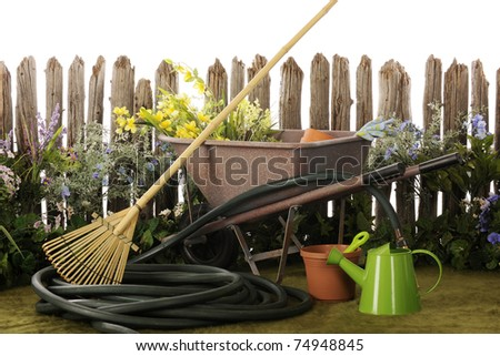 Flowers and garden tools by a weather, old picket fence.