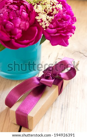 Flowers and present box with ribbon on table. Romantic gift.Valentines\'s day.