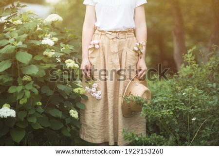 flowers and shrubs in summer Ornamental garden. girl woman in linen skirt and hat on path of Park. Gardening and Landscaped Stock photo ©