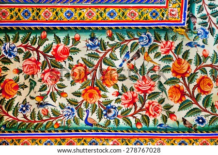 Flowers and small birds design on colorful fresco of historical mansion in Rajasthan, India