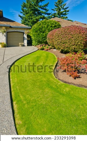 Flowers and stones and nicely trimmed bushes in front of the house, front yard. Landscape design.