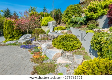 Flowers and stones in front of the house, front yard. Landscape design.