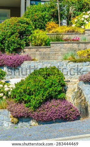 Flowers and stones on different levels in front of the house, front yard. Landscape design. Vertical.