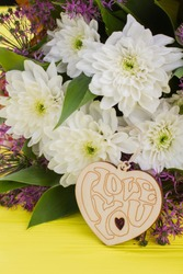 Flowers and wooden heart. Valentines Day heart with inscription Love you and bouquet of flowers. Love and romance concept.