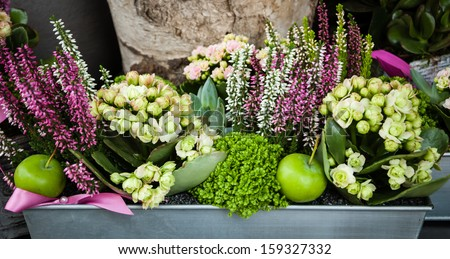 Flowers arrangement with green apples and pink bow in metal box at the entry to the flower shop.