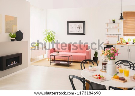 Flowers at table in white apartment interior with poster above pink settee near fireplace. Real photo #1173184690