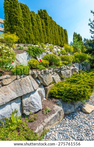 Flowers, bushes and stones in front of the house, front yard. Landscape design.