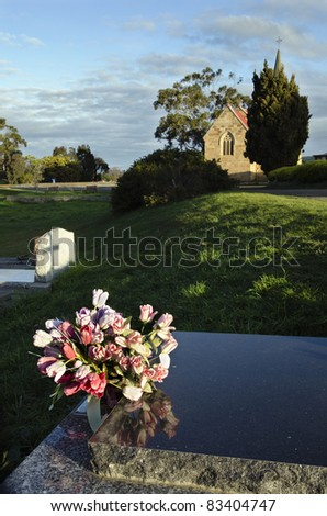 Flowers, church and shadow of cross on gravestone in urban graveyard. Richmond, Tasmania, Australia.