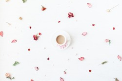 Flowers composition. Cup of coffee, dried flowers and leaves. Top view, flat lay