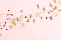 Flowers composition. Frame made of dried rose flowers on pink background.