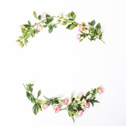 Flowers composition. Frame made of dried rose flowers on white wooden background.