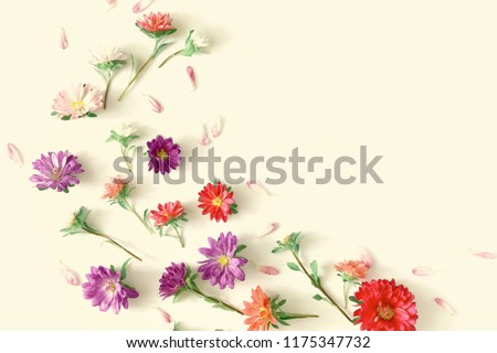 Stock Photo Flowers composition.  Frame made of fresh fall flowers on light pastel yellow  background. Flat lay, top view, copy space