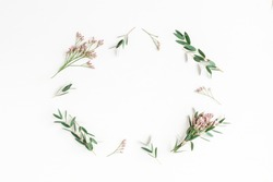 Flowers composition. Frame made of pink flowers and eucalyptus branches on white background. Flat lay, top view.