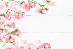 Flowers composition. Frame made of pink rose flowers on white wooden background. Flat lay, top view, copy space