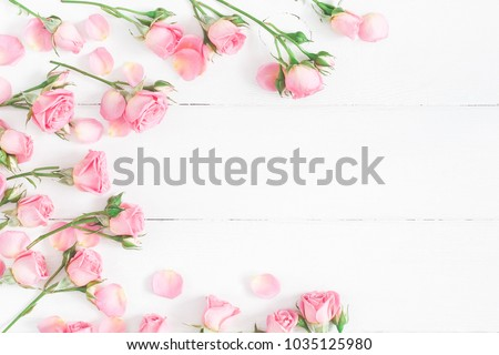 Flowers composition. Frame made of pink rose flowers on white wooden background. Flat lay, top view, copy space #1035125980